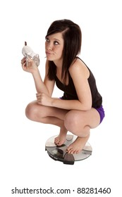 a woman kneeling on a weight scale holding her candy bar with a funny expression.