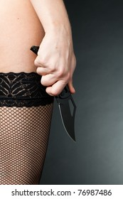A woman with a knife in erotic stockings (violence background)
