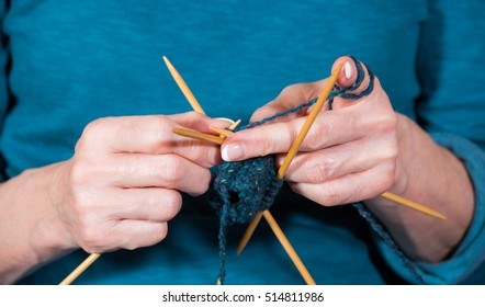 A woman knits traditionally in handwork