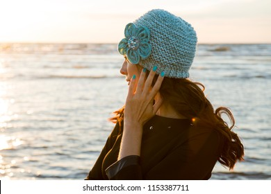 The woman in a knitted cap with a flower, admires a sea sunset