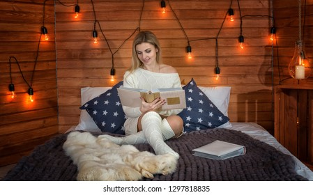 A woman in knitted clothes is sitting on a bed in a country house and reads books.