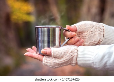 Woman with knitted fingerless glove is holding mug with steaming hot drink. Refreshment during hike in nature. Hot coffee or tea in metal cup