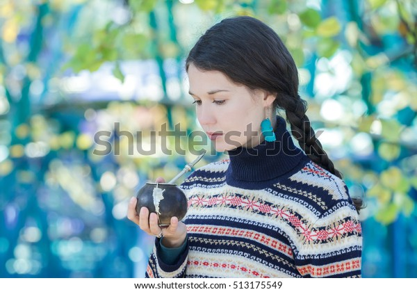 Woman in knitted snowflakes pattern sweater and turquoise earrings is drinking hot yerba mate