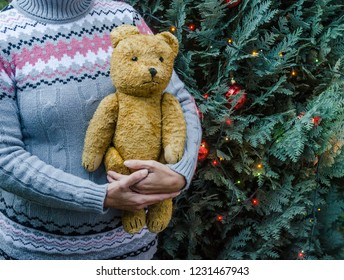 Woman in knitted sweater holding an old teddy bear next to the decorated christmas tree