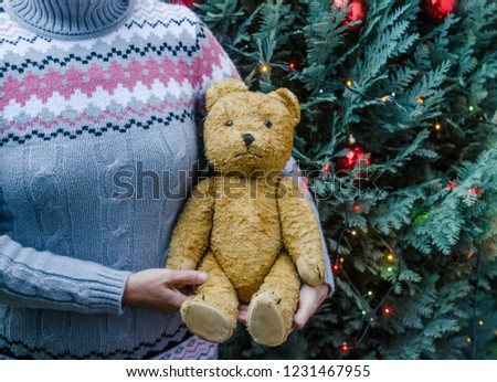 77a597e8f1 Woman in knitted sweater holding an old teddy bear next to the decorated christmas  tree