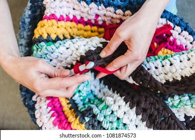 The woman is knitting crocheted out of thick yarn. Yarn from old clothes. Rug of homemade thread. Female hands hold the hook. Vintage carpet. Knitted plaid. Handmade. Home hobby.