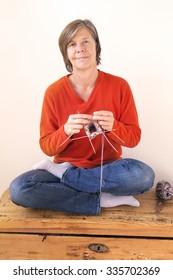 woman knitting and smiles at camera