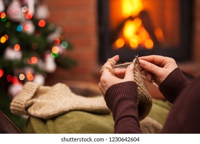 Woman knitting woolen socks sitting by the christmas tree and fireplace in the holidays season evening - closeup