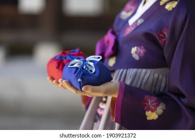 Woman in Korean traditional clothes  holding traditional packages  - Shutterstock ID 1903921372