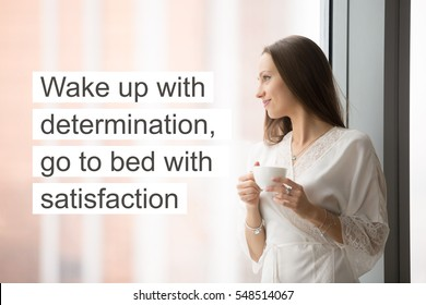 """Woman in lace night gown relaxing at cozy home, feeling happy, looking through the window with a cup of drink. Photo with motivational text """"Wake up with determination, go to bed with satisfaction"""""""