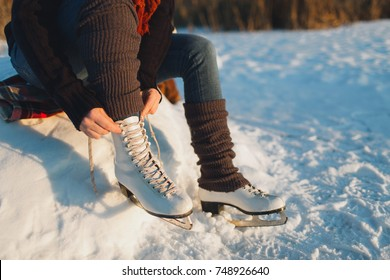 Woman lacing ice skates at the edge of a frozen lake. Cropped image of a woman putting ice skates on.