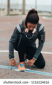 Woman lacing sport footwear before running or exercising. Outdoor city workout concept. Female fitness athlete getting ready for working out.