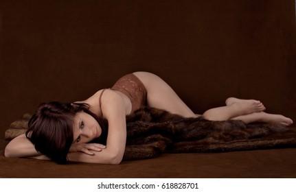 Woman in Lacy Brown Bodysuit Lying on Fur Blanket