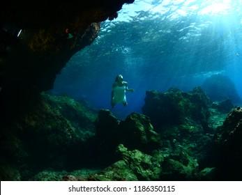 woman lady free diving apnea underwater cave