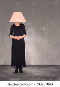 Woman with lampshade on head. Ageing concept as women become invisible with age, or just embarrassment, bad hair day!