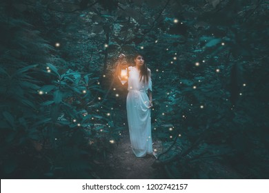 Woman with lantern walking in the misty forest in rustic white dress. Beautiful fairy tale