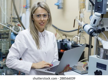 Woman with laptop computer working in chemical lab