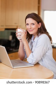 Woman with laptop and a cup in the kitchen