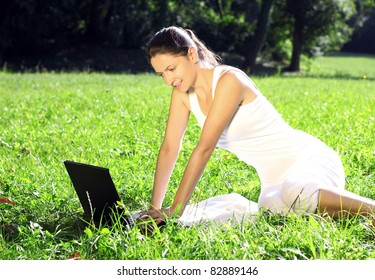 Woman with laptop enjoying in park