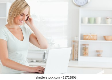 Woman with a laptop and a phone searching on the internet in the kitchen