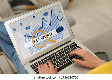 Woman with laptop searching for keyword at home, closeup
