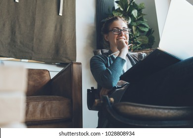 Woman with laptop sitting in cozy apartment