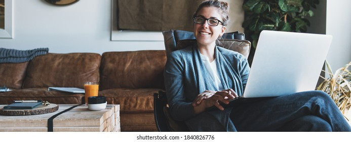 Woman with laptop sitting in cozy creative working space. Wide screen, panoramic