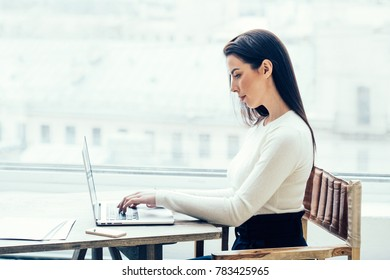 Woman with laptop sitting near table  window freelance