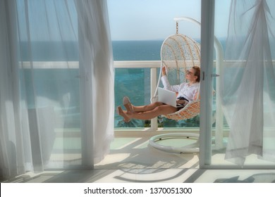 Woman with laptop taking rest in hotel terrace over sea view