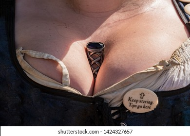 Woman with large breasts in Renaissance period dress and a dagger stuck in her cleavage at a Renaissance Fair.