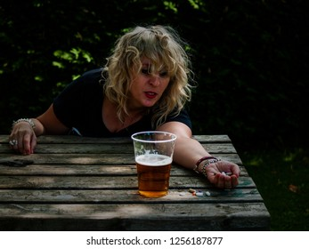 A woman with a large number of pills in her hand of different colors and sizes and a glass of beer, at an outdoor table