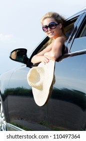 Woman with a large wide brimmed straw hat leaning out of the open window of a car