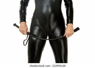 Woman in latex suit holding a leather whip