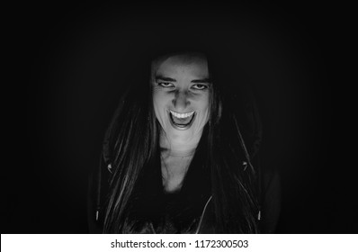 Woman laughing hysterically in the dark