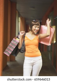 woman laughing while holding up shopping bags