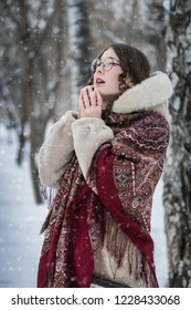 woman laughs in cold winter day outdoors in a snowy park among trees.