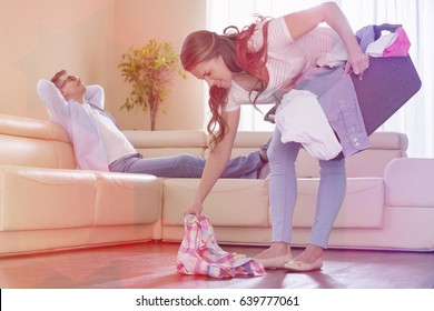 Woman with laundry basket picking clothes while man relaxing on sofa in background
