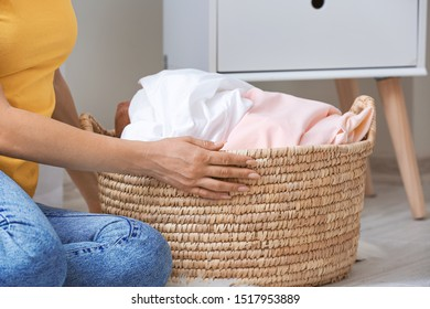 Woman with laundry sitting on floor in room