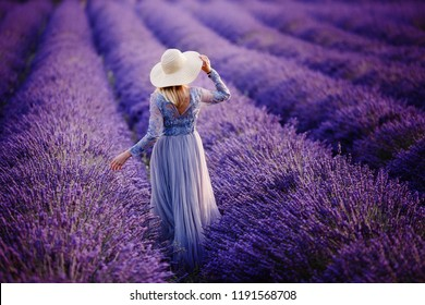 Woman in lavender flowers field at sunset in purple dress. France, Provence.
