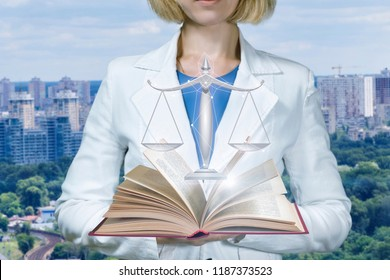 Woman lawer shows the book and scales of justice on the background of the city.