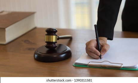 Woman  lawyer working with contract papers and reading law book in a courtroom