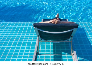 Woman lay down relax on wooden daybed in blue water of swimming pool. (Selective focus)