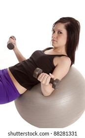 a woman laying back on her exercise ball holding her weights.