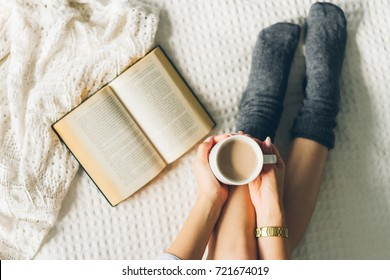woman laying in bed and read book with cup if coffee.