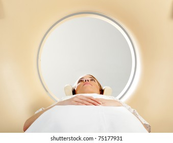 A woman laying down with eyes open having a CT scan