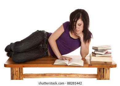 A woman laying down on a bench with a stack of books reading.
