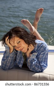 A woman laying on the back of the boat in a plaid shirt.