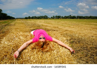 Woman Laying on Bale of Hay