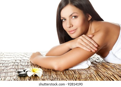 woman laying on bamboo mat in spa salon, looking at camera