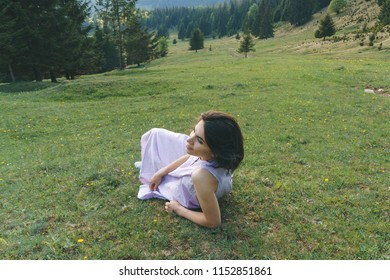 woman laying on green meadow and enjoying view on forest